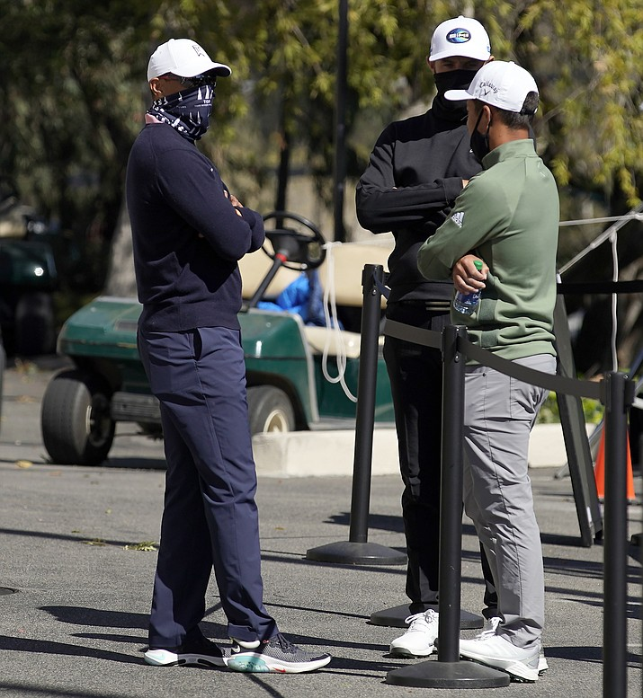 Tiger Woods, Dustin Johnson and Xander Schauffele talk after high winds suspended play during the third round of the Genesis Invitational golf tournament at Riviera Country Club, Saturday, Feb. 20, 2021, in the Pacific Palisades area of Los Angeles. (Ryan Kang/AP)