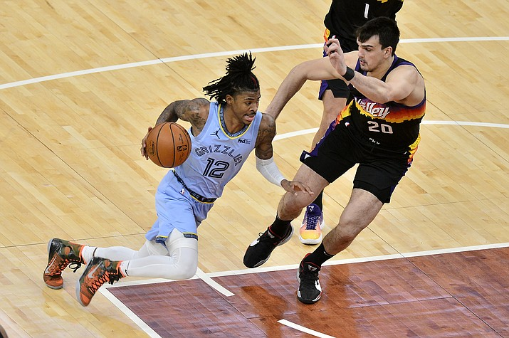 Memphis Grizzlies guard Ja Morant (12) drives against Phoenix Suns forward Dario Saric (20) in the second half of an NBA basketball game Saturday, Feb. 20, 2021, in Memphis, Tenn. (Brandon Dill/AP)