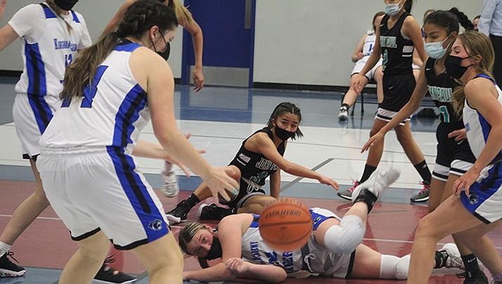 Players scramble for a loose ball during Kingman Academy's 44-43 loss to visiting St. John Paul II on Thursday, Feb. 18 in Kingman. (Photo by Casey Jones/Kingman Miner)