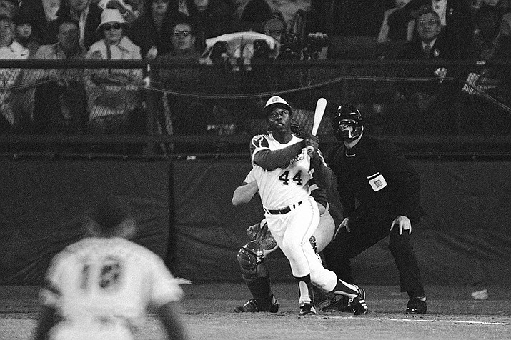 Atlanta Braves' Hank Aaron eyes the flight of the ball after hitting his 715th career homer in a game against the Los Angeles Dodgers in Atlanta, Ga., in this Monday night, April 8, 1974, file photo. Aaron broke Babe Ruth's record of 714 career home runs. Dodgers southpaw pitcher Al Downing, catcher Joe Ferguson and umpire David Davidson look on. (Harry Harrris/AP)