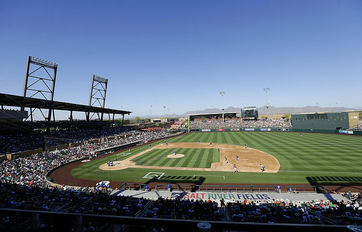In this March 18, 2016, file photo, fans at Salt River Fields at Talking Stick watch a spring training baseball game between the Arizona Diamondbacks and the Los Angeles Dodgers in Scottsdale, Ariz. The Diamondbacks sold out their entire spring allotment of tickets in less than 24 hours after they went on sale to the public. Approximately 2,200 tickets were sold for all 14 of the team's home games, with fans spread throughout the park in pods of two, four or six seats and masks are required except when eating or drinking. (AP Photo/Jeff Chiu, File)