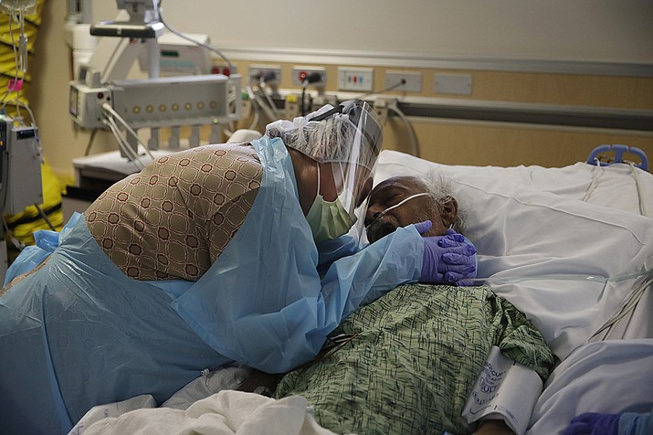 In this July 31, 2020, file photo, Romelia Navarro, 64, weeps while hugging her husband, Antonio, in his final moments in a COVID-19 unit at St. Jude Medical Center in Fullerton, Calif. The U.S. death toll from COVID-19 has almost topped 500,000 — a number so staggering that a top health researchers says it is hard to imagine an American who hasn't lost a relative or doesn't know someone who died. (Jae C. Hong, File)