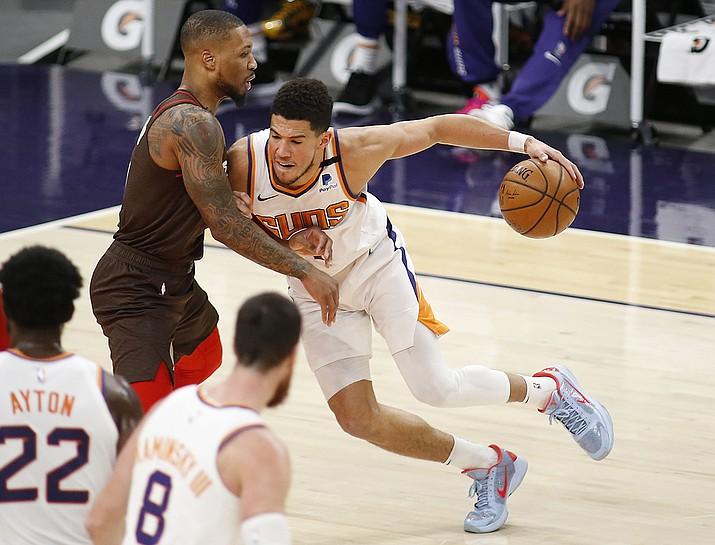 Phoenix Suns' Devin Booker muscles his way towards the basket against Portland Trail Blazers' Damien Lillard during the first half of an NBA basketball game Monday, Feb. 22, 2021, in Phoenix. (Darryl Webb/AP)