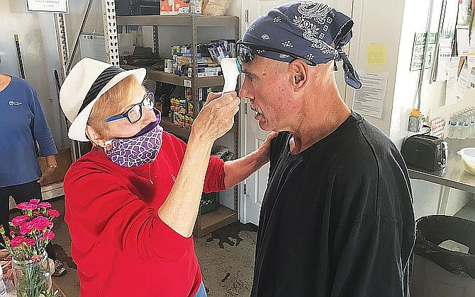 A volunteer takes the temperature of a Verde Valley Homeless Coalition drop-in center last year. The Cottonwood Planning and Zoning Commission approved a use permit modification Monday to include a fire suppression sprinkler system plan. VVN file