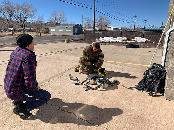 Williams Fire Assistant Chief Don Mackay works with a new recruit on donning an SCBA pack during a training Feb. 20. (Loretta Mckenney/WGCN)