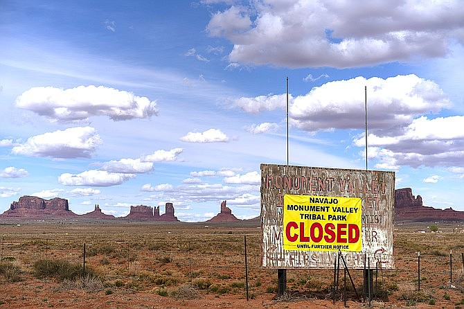 A sign is posted at the entrance of Monument Valley in Oljato-Monument Valley, Utah, on the Navajo reservation in April 2020 announcing the closure of the tribal park. Since the coronavirus pandemic began, the reservation has reported some of the highest number of cases in the country. Now, the tribe is making vaccinations a priority for all members. (AP Photo/Carolyn Kaster)
