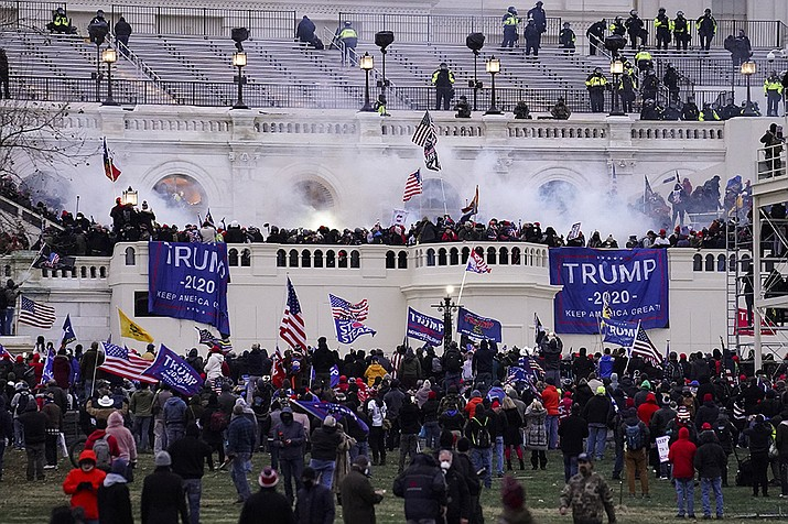 In this Wednesday, Jan. 6, 2021, file photo, violent protesters storm the Capitol, in Washington. People charged in the attack on the U.S. Capitol left behind a trove of videos and messages that have helped federal authorities build cases. In nearly half of the more than 200 federal cases stemming from the attack, authorities have cited evidence that an insurrectionist appeared to have been inspired by conspiracy theories or extremist ideologies, according to an Associated Press review of court records. (John Minchillo, AP File)