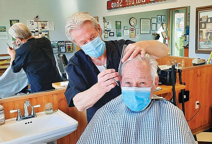 Dennis Errera cuts the hair of Gordie Garvey on a recent February day. Errera is retiring March 5. VVN/Jason W. Brooks