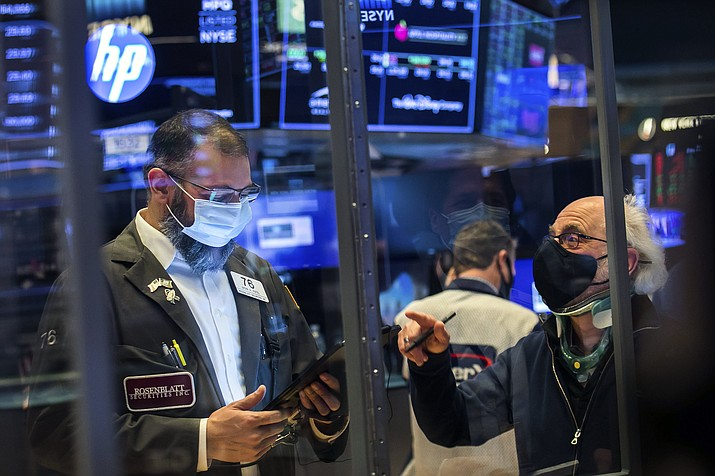 In this photo provided by the New York Stock Exchange, traders Aman Patel, left, and Peter Tuchman work on the floor, Friday, Feb 26, 2021. Stocks wobbled between small gains and losses on Wall Street Friday as rising technology stocks offset a slide in banks and energy companies. (Courtney Crow/New York Stock Exchange via AP)