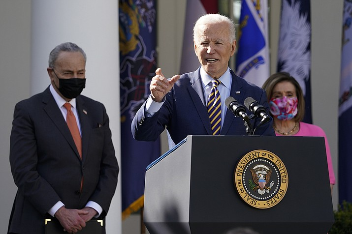 President Joe Biden speaks about the American Rescue Plan, a coronavirus relief package, in the Rose Garden of the White House, March 12, in Washington D.C. Senate Majority Leader Chuck Schumer of New York, left, and House Speaker Nancy Pelosi of California, listen. (AP Photo/Alex Brandon)