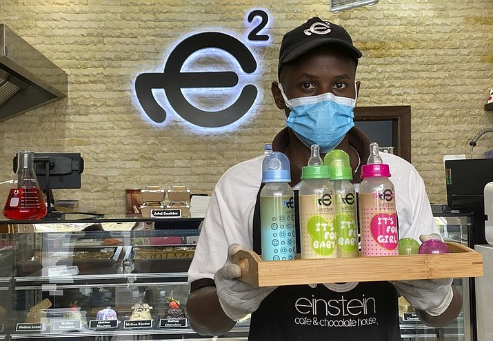 A waiter poses with a tray of baby bottles that he brought out from storage, at Einstein Cafe in Dubai, United Arab Emirates, Sunday, March 14, 2021. Cafes across several Gulf Arab states have begun selling coffee and other cold drinks in baby bottles, kicking off a new trend that has prompted excitement, confusion and backlash. The fad started at Einstein Cafe, a slick dessert chain with branches across the region. Soon, authorities from Kuwait to Dubai cracked down claiming the trend violates local traditions. (AP Photo/Kamran Jebreili)