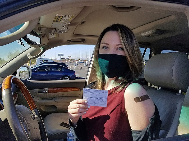Emily Alexander, 37, shows her COVID-19 vaccination card shortly after getting the vaccine in the parking lot of the State Farm Stadium in Glendale on Monday, Jan. 11, 2021. Just over 1 million Arizona residents are now fully vaccinated against COVID-19, state officials announced Tuesday, March 16, 2021. (Terry Tang/AP, file)