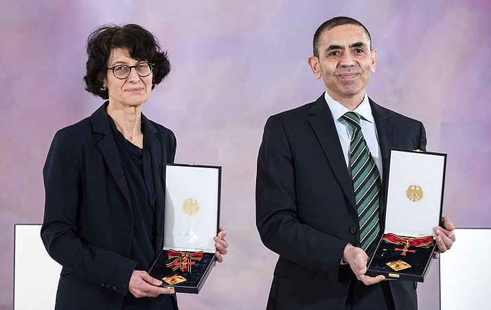 Ugur Sahin and his wife Ozlem Tureci, founders of the Mainz-based coronavirus vaccine developer BioNtech, stand during the award of the Grand Cross of Merit with Star of the Order of Merit of the Federal Republic of Germany by President Steinmeier at Bellevue Palace in Berlin, Germany, Friday, March 19, 2021. (Bernd von Jutrczenka/dpa AP)