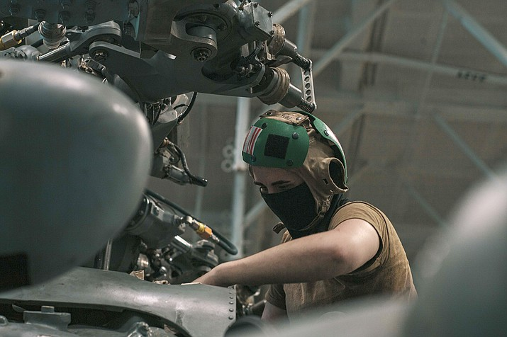 """U.S. Navy Aviation Structural Mechanic 3rd Class Rachel Womack, from Prescott, is assigned to the """"Eightballers"""" of Helicopter Sea Combat Squadron (HSC) 8. In this photo, Womack wipes the rotor head of an MH-60S Sea Hawk in the hangar bay of the aircraft carrier USS Theodore Roosevelt (CVN 71) March 16, 2021. The Theodore Roosevelt Carrier Strike Group is on a scheduled deployment to the U.S. 7th Fleet area of operations in the Indian Ocean. As the U.S. Navy's largest forward-deployed fleet, 7th Fleet routinely operates and interacts with 35 maritime nations while conducting missions to preserve and protect a free and open Indo-Pacific Region. With more than 90% of all trade traveling by sea, and 95% of the world's international phone and internet traffic carried through fiber optic cables lying on the ocean floor, Navy officials continue to emphasize that the prosperity and security of the United States is directly linked to a strong and ready Navy. (Mass Communication Specialist Seaman Alexander B. Williams)"""