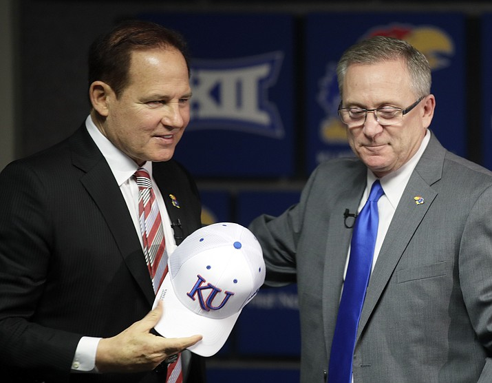 In this Nov. 18, 2018 photo, Les Miles, left, is introduced as Kansas football coach by athletic director Jeff Long, right, during a news conference in Lawrence, Kan. Kansas has fired athletic director Jeff Long less than two days after mutually parting with Les Miles amid sexual misconduct allegations dating to the football coach's time at LSU, a person familiar with the decision told The Associated Press on Wednesday, March 10, 2021. (Orlin Wagner/AP, File)