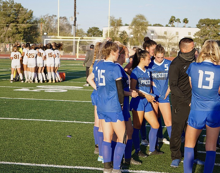 The Prescott girls soccer team huddles up with head coach Paul Campuzano while Salpointe Catholic celebrates after the Lancers defeated the Badgers 2-0 in the 4A State Finals on Saturday, March 20, 2021, at Coronado High School in Scottsdale. (Aaron Valdez/Courier)
