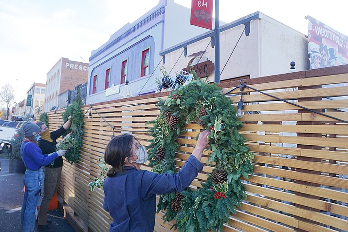 The Raven Cafe on Cortez Street has one of the three parklets in downtown Prescott that have been installed on city rights-of-way as a way to allow outdoor dining during the COVID-19 pandemic. Pictured are Shanti Rade of Whipstone Farm, right, and Emily Ahrendt, left, and Emily Wilson, center, of Prescott Gardener working to put up fresh wreaths in December 2020. On March 23, 2021, the Prescott City Council decided all parklets should come down by the end of April. (Cindy Barks/Courier, file)