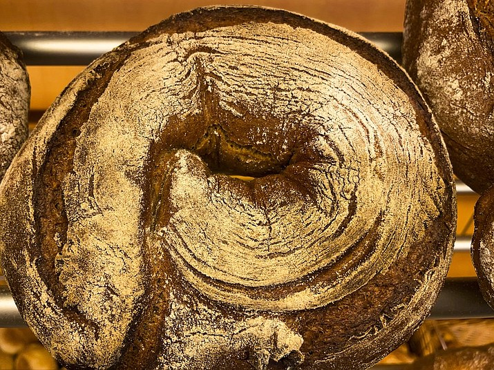 A bread loaf that was baked with beer is displayed in the Coelven bakery in Duesseldorf, Germany, Tuesday, March 23, 2021. About 6,000 litres of the renowned copper-colored 'Altbier' of the historic Fuechschen brewery remain unsold and nearing its expiry date. The brewery now works with craft bakers who use the beer to make bread, with about twelve bakeries producing the grain bread and are giving the additional bonus of a bottle of Fuechschen's Altbier free of charge with every loaf.(AP Photo/Daniel Niemann)