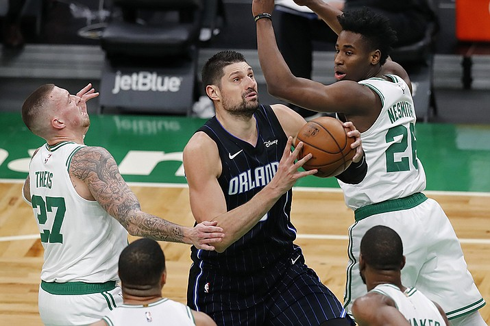 Orlando Magic's Nikola Vucevic (9) drives past Boston Celtics' Daniel Theis (27) and Semi Ojeleye (37) during the second half on an NBA basketball game, Sunday, March 21, 2021, in Boston. (Michael Dwyer/AP)