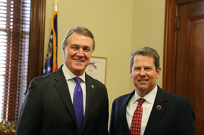 Georgia Gov. Brian Kemp, right, shown with former Georgia Sen. David Purdue, has signed a controversial bill that includes restrictions on voting by mail, and giving greater control over how elections are conducted to the state Legislature. (Office of U.S. Sen. David Perdue photo/Public domain)