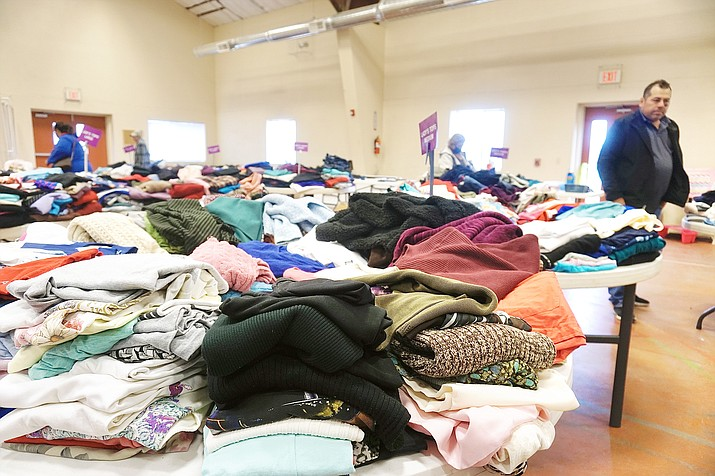 Clothes are laid out on tables inside the gym of the First Southern Baptist Church in Chino Valley during a clothing giveaway. Families in need from the Chino Valley, Paulden and Ash Fork communities can attend the quarterly giveaways to pick out clothes and other items for free. (Aaron Valdez/Review)