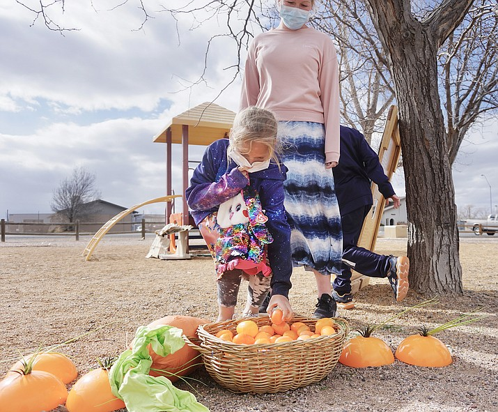 An attendee takes an Easter egg from a basket after completing a station task at the Chino Valley Public Library's Easter-themed Storywalk on Thursday, March 25, 2021, at Memory Park. (Aaron Valdez/Courier)