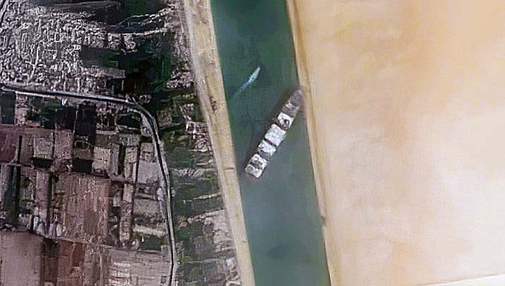 "This satellite photo shows the ""Ever Given"" container ship wedged in the Suez Canal. It blocked traffic through the vital canal for nearly a week before being freed on Monday, March 29. (Photo by Pierre Markuse, cc-by-sa-2.0, https://bit.ly/3tVX3TA)"