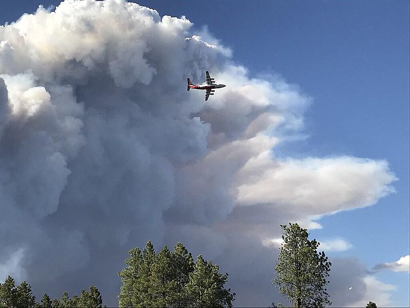 An air tanker flies near the Mangum Fire smoke column in June 2020.