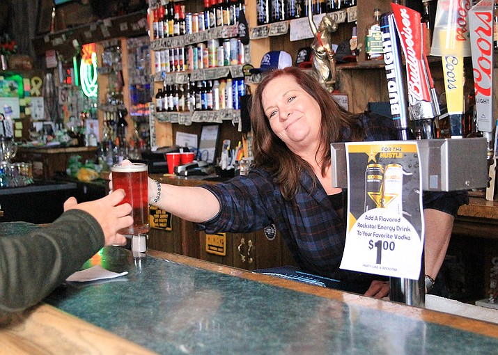 Laurie Arnberger serves a drink at the Sultana Bar March 26 after Gov. Doug Ducey announced an executive order reopening bars and nightclubs. (Wendy Howell/WGCN)