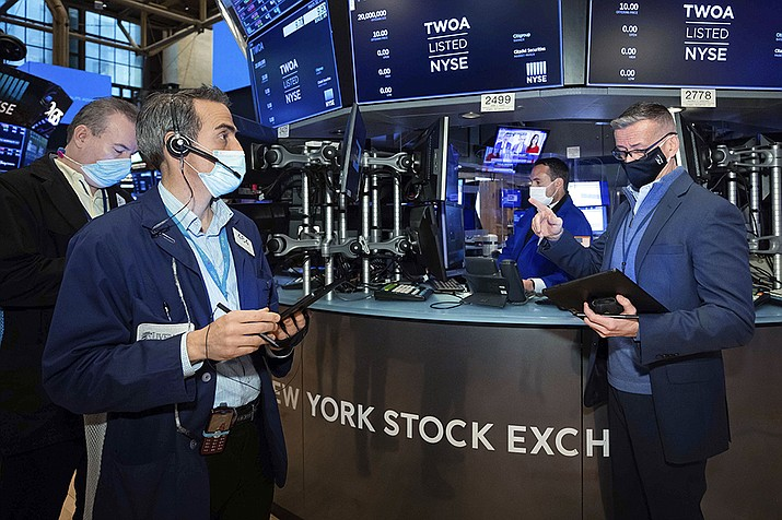 In this photo provided by the New York Stock Exchange, traders Gregory Rowe, foreground left, and Neil Catania, right, work on the floor. Tuesday, March 30, 2021. U.S. stock indexes are edging lower in midday trading on Tuesday as another swell higher for Treasury yields adds pressure on big technology stocks. (Colin Ziemer/New York Stock Exchange via AP)