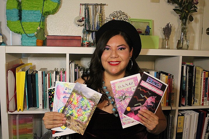 Amber McCrary holds up zines and a chapter book she created. McCrary is one of several authors presenting at the Northern Arizona Book Festival April 1-4. (Photo courtesy of Amber McCrary)