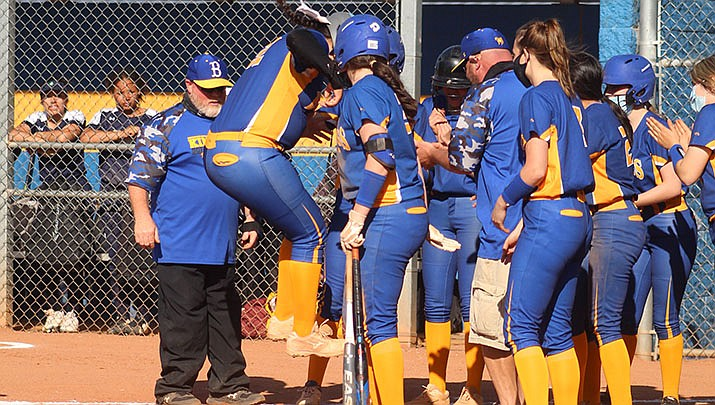 Kingman shortstop Maddy Chamberlain, surrounded by her teammates, jumps on home plate after hitting a three-run homer in a 25-1 win over Yuma Catholic on Tuesday, March 30. (Photo by Casey Jones/Kingman Miner)