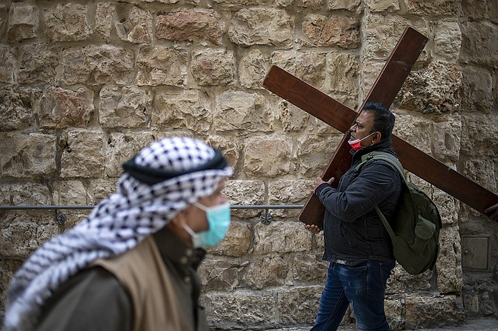 A Christian carries a cross as he walks along the Via Dolorosa towards the Church of the Holy Sepulchre, traditionally believed by many to be the site of the crucifixion of Jesus Christ, during the Good Friday procession in Jerusalem's old city, Friday, April 2, 2021. (Ariel Schalit/AP)