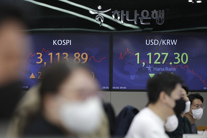 Currency traders watch computer monitors near screens showing the Korea Composite Stock Price Index (KOSPI), left, and the foreign exchange rate between U.S. dollar and South Korean won at the foreign exchange dealing room of the KEB Hana Bank headquarters in Seoul, South Korea, Friday, April 2, 2021. Asian shares were higher Friday after a broad rally pushed the S&P 500 past 4,000 points for the first time. (Lee Jin-man/AP)