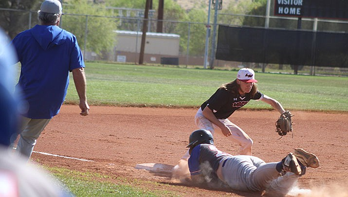Gunner Markins of Moon Valley slides safely back into third, beating the tag by Lee Williams third-baseman Levi Isaacs. (Photo by Casey Jones/Kingman Miner)