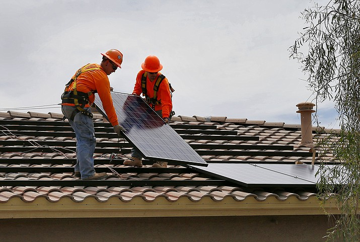 In this July 28, 2015, file photo, electricians, Adam Hall, right, and Steven Gabert install solar panels on a roof for Arizona Public Service company in Goodyear, Ariz. The 6-4 vote by the Senate Appropriations Committee on March 31, 2021, followed arguments by Rep. Gail Griffin, R-Hereford, that it was wrong of the independently elected utility regulators to propose that half of the state's energy be generated by carbon-free sources by 2035 and have power be totally carbon free by 2050. (Matt York/AP, file)
