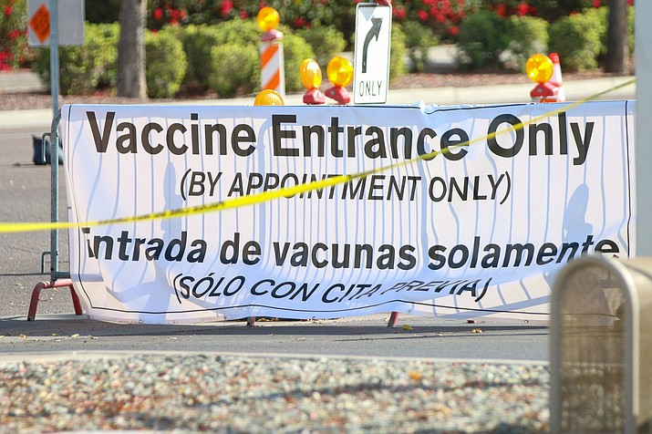 A sign directs cars at the vaccination site at State Farm Stadium in Glendale. Data shows some predominantly Hispanic and impoverished neighborhoods have far lower vaccination rates than those that are mostly white and well-off. (Photo by Marlee Smith/Cronkite News)