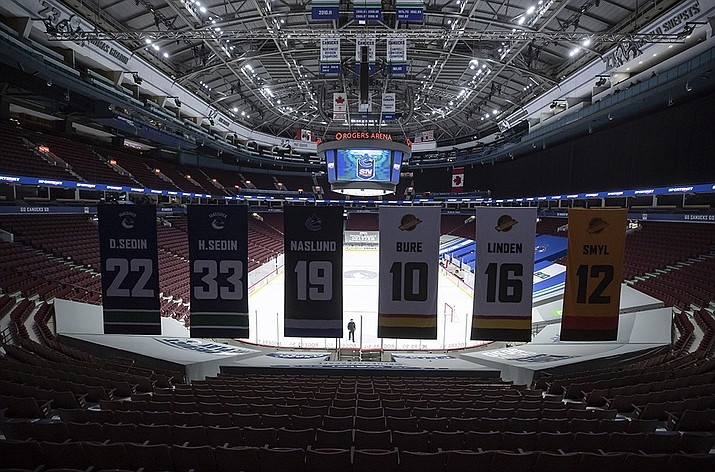 An arena worker removes the net from the ice after the Vancouver Canucks and Calgary Flames NHL hockey game was postponed due to a positive COVID-19 test result, in Vancouver, British Columbia, Wednesday, March 31, 2021. (Darryl Dyck/The Canadian Press via AP)