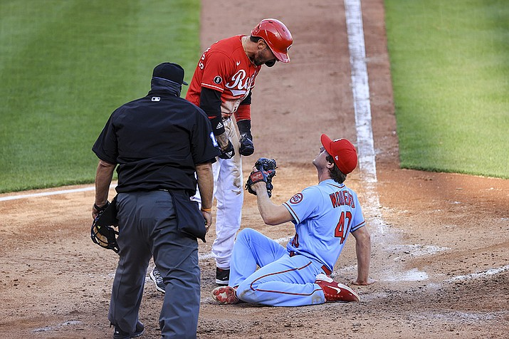 Cincinnati Reds' Nick Castellanos, center, reacts after scoring a run ahead of the tag by St. Louis Cardinals' Jake Woodford, right, during the fourth inning of a baseball game in Cincinnati, Saturday, April 3, 2021. (Aaron Doster/AP)