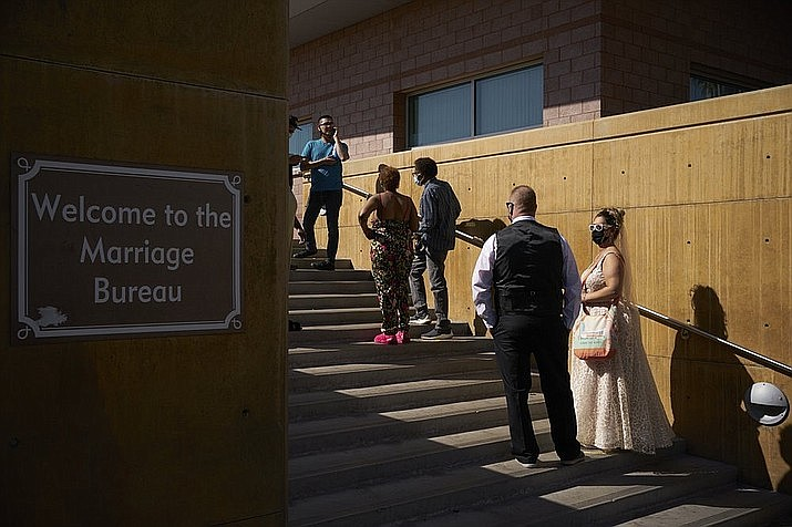 Couples wait in line for marriage licenses at the Marriage License Bureau, Friday, April 2, 2021, in Las Vegas. The bureau was seeing busier than normal traffic ahead of 4/3/21, a popular day to get married in Las Vegas. (AP Photo/John Locher)