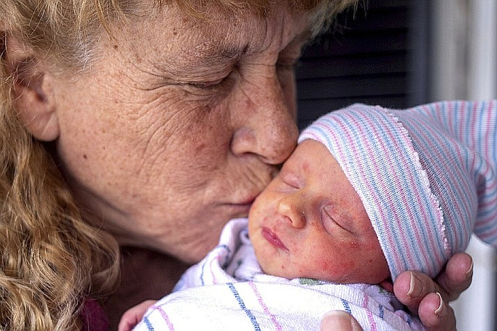 Barbara Higgins cradles her newborn's head in her the family home on Wednesday, March 24, 2021 in Concord, N.H. Higgins who lost her 13-year-old daughter to a brain tumor in 2016 has given birth to a son at age 57. Barbara Higgins, and her husband, Kenny Banzhoff, of Concord, have been dealing with grief over the death of their daughter, Molly. (Geoff Forester/The Concord Monitor via AP)