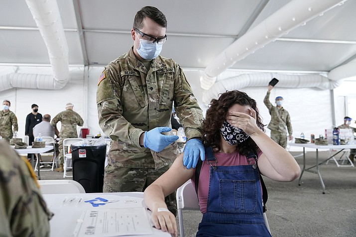 In this April 5, 2021, file photo, Leanne Montenegro, 21, covers her eyes as she doesn't like the sight of needles, while she receives the Pfizer COVID-19 vaccine at a FEMA vaccination center at Miami Dade College in Miami. Nearly half of new coronavirus infections nationwide are in just five states, including Florida — a situation that puts pressure on the federal government to consider changing how it distributes vaccines by sending more doses to hot spots.  (Lynne Sladky, AP File)