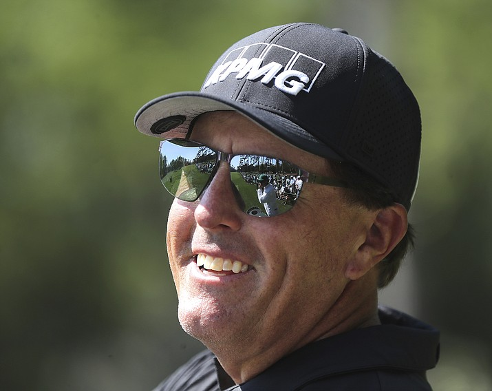Phil Mickelson is all smiles sharing a laugh with the patrons while he tees off on the 14th hole during his practice round for the Masters at Augusta National Golf Club on Tuesday, April 6, 2021, in Augusta, Ga. (Curtis Compton/Atlanta Journal-Constitution via AP)