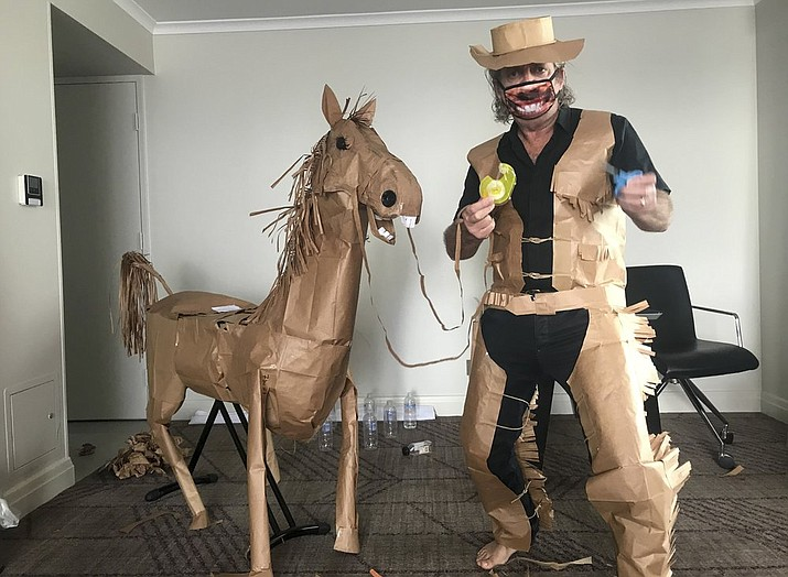 "David Marriott poses with his paper horse ""Russell"" in his hotel room in Brisbane, Australia, April 1, 2021. While in quarantine inside his Brisbane hotel room, the art director was bored and started making a cowboy outfit from the paper bags his meals were being delivered in. His project expanded to include a horse and a clingfilm villain that he has daily adventures with, in images that have gained a huge online following. (David Marriott via AP)"