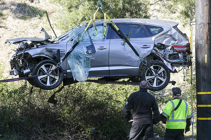 In this Feb. 23, 2021, file photo, a crane is used to lift a vehicle following a rollover accident involving golfer Tiger Woods, in the Rancho Palos Verdes suburb of Los Angeles. Authorities said Wednesday, April 7, Woods was speeding when he crashed leaving him seriously injured. (Ringo H.W. Chiu, AP File)
