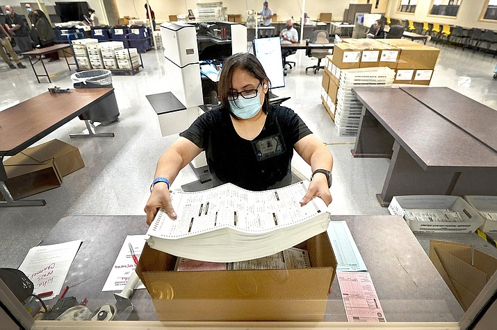This Nov. 6, 2020, file photo shows an Arizona election official working with ballots inside the Maricopa County Recorder's Office in Phoenix. In a letter Tuesday, April 6, 2021, to Doug Logan, the CEO of Cyber Ninjas, lawyers claim tactics planned by election auditors hired by the Senate to verify the outcome of the 2020 race are illegal and even criminal, attorneys for various voter rights issues contend. (Matt York/AP, file)