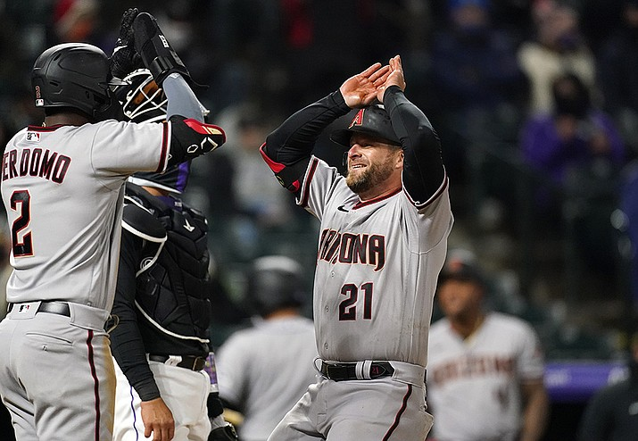 Arizona Diamondbacks Geraldo Perdomo, left, waits to congratulate Stephen Vogt as he crosses home plate after hitting a two-run home run off Colorado Rockies relief pitcher Yency Almonte in the seventh inning of a baseball game Tuesday, April 6, 2021, in Denver. (David Zalubowski/AP)
