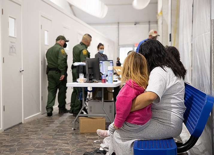 A woman and young girl wait to be processed by Customs and Border Protection officials after being apprehended at the southern border in March. The majority of migrants are still turned away at the border as a COVID-19 precaution. (Photo by Jerry Glaser Sr./Customs and Border Protection)