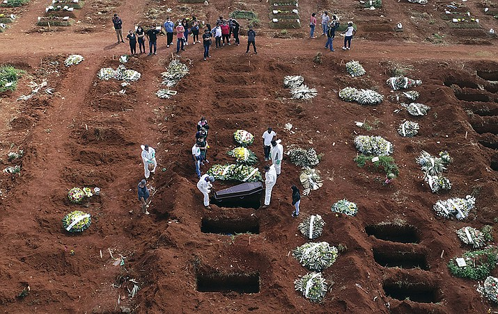 In this April 7, 2021, file photo, cemetery workers wearing protective gear lower the coffin of a person who died from complications related to COVID-19 into a gravesite at the Vila Formosa cemetery in Sao Paulo, Brazil. Nations around the world set new records Thursday, April 8, for COVID-19 deaths and new coronavirus infections, and the disease surged even in some countries that have kept the virus in check. Brazil became just the third country, after the U.S. and Peru, to report a 24-hour tally of COVID-19 deaths exceeding 4,000. (Andre Penner, AP File)