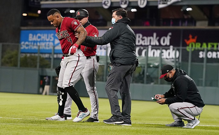 Arizona Diamondbacks' Ketel Marte, left, is helped off the field after injuring his leg while running out a ground ball during the sixth inning of the team's baseball game against the Colorado Rockies on Wednesday, April 7, 2021, in Denver. (David Zalubowski/AP)
